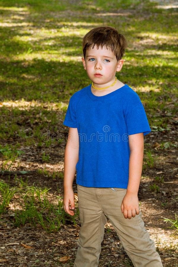 Exhausted and Sweaty Little Boy Stands Slumped With Arms Hanging royalty free stock images