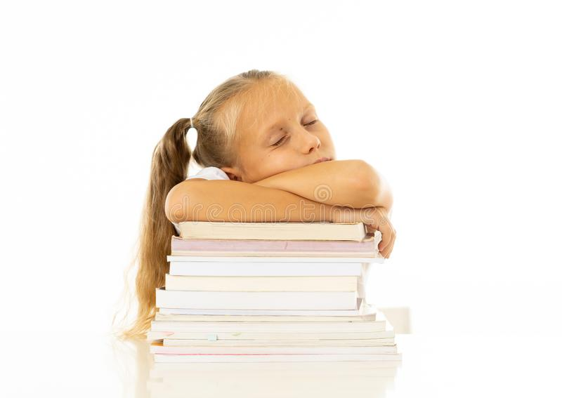 Exhausted sweet cute blonde girl sleeping on a pile of schoolbooks after being studying hard isolated on a withe background in too stock photos