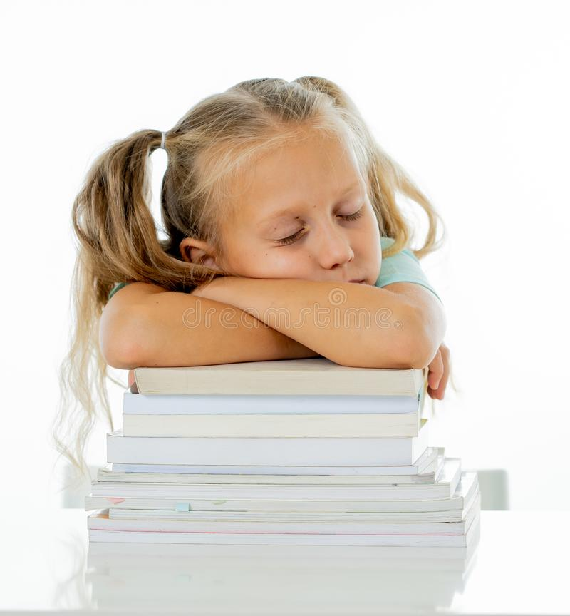 Exhausted sweet cute blonde girl sleeping on a pile of schoolbooks after being studying hard isolated on a withe background in too royalty free stock image