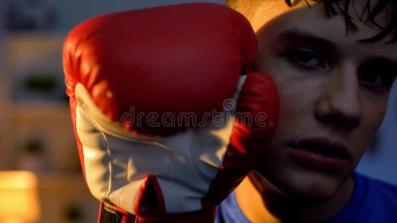 Exhausted teenager holding hand in boxing glove near face looking into camera royalty free stock image