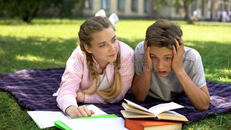 Exhausted teenagers bored with studying, lying on plaid near college campus royalty free stock images