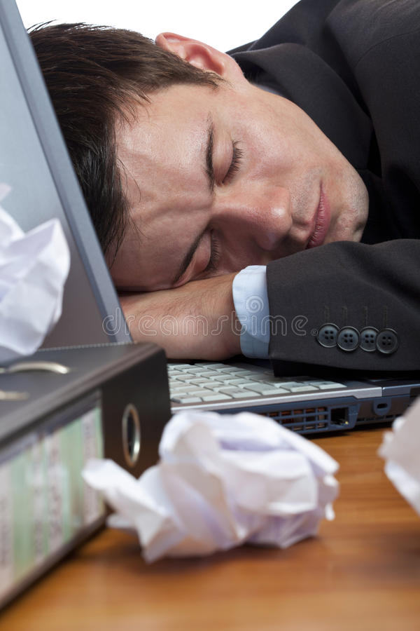 Exhausted, tired businessman sleeping at desk. Close-up of exhausted, tired businessman sleeping at desk royalty free stock images