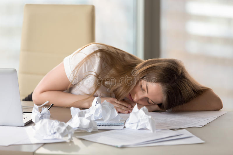 Exhausted tired woman sleeping at desk after overwork in office. Tired woman sleeping at desk exhausted by overwork, dozing employee lying asleep on hand at royalty free stock photos