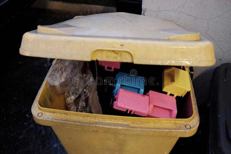 Exhausted toner cartridges the garbage bin. Exhausted toner cartridges in the garbage bin stock image