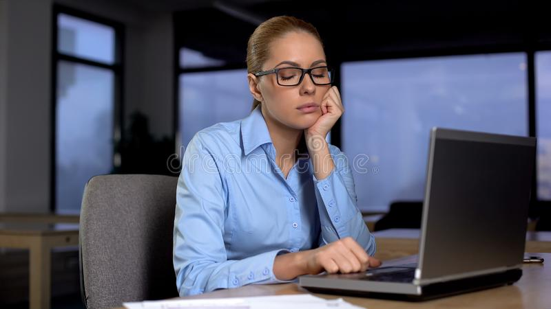 Exhausted woman with closed eyes resting in office, lack of sleep busy lifestyle. Stock photo royalty free stock image