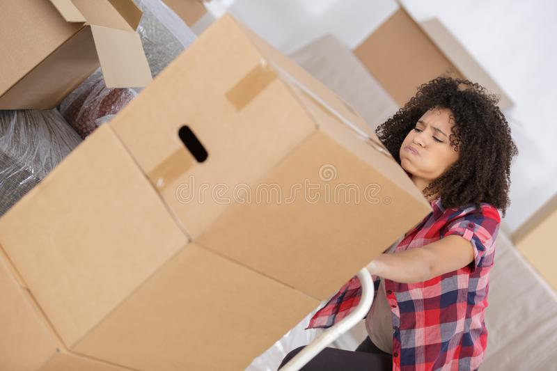 Exhausted woman pushing trolley full boxes stock photography