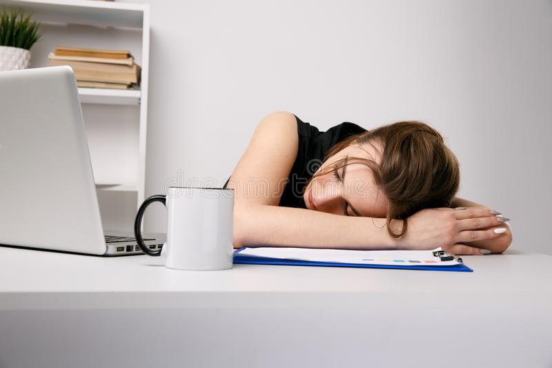 Exhausted woman sleeping at her office desk near the computer. stock photos