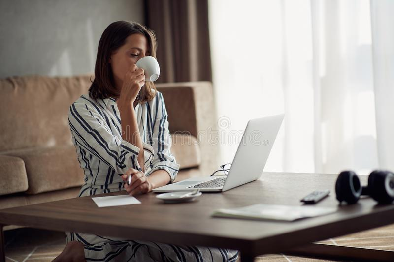 Exhausted woman working at home with a laptop and drinking coffee stock photos