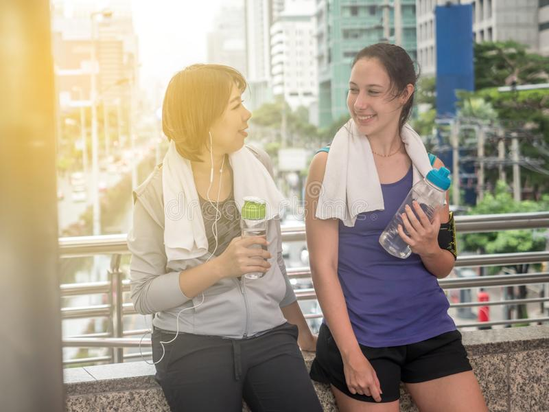 Exhausted after workout. Attractive young woman in sportswear drinking water while standing outdoor. They smile to each other stock image