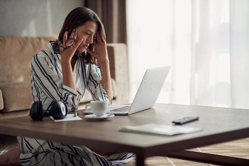 Exhausted and worried woman working at home with a laptop stock photo