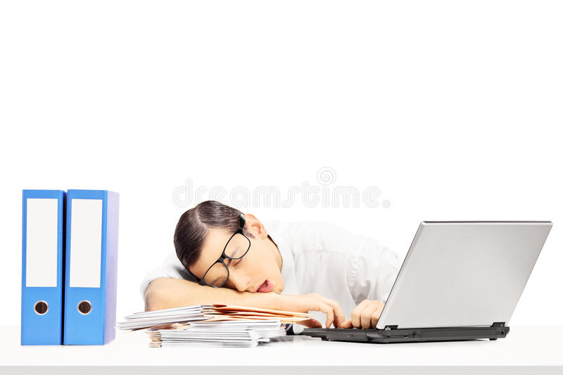 Exhausted young businessman sleeping on a desk at his workplace. Isolated on white background stock image