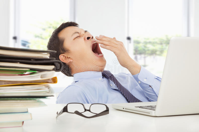 Exhausted young businessman yawning at work stock images
