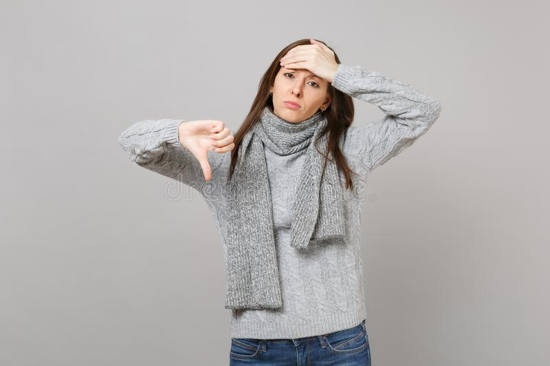 Exhausted young woman in gray sweater, scarf holding hand on forehead having headache showing thumb down on royalty free stock photography