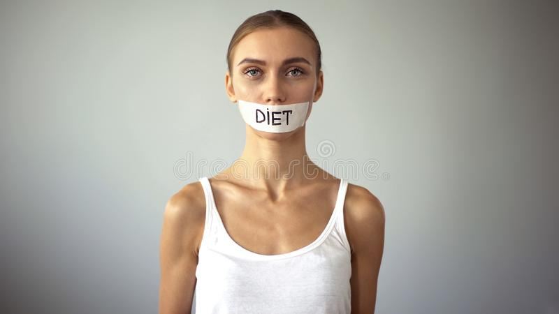 Exhausting diet concept, miserable slim woman with taped mouth looking at camera royalty free stock images