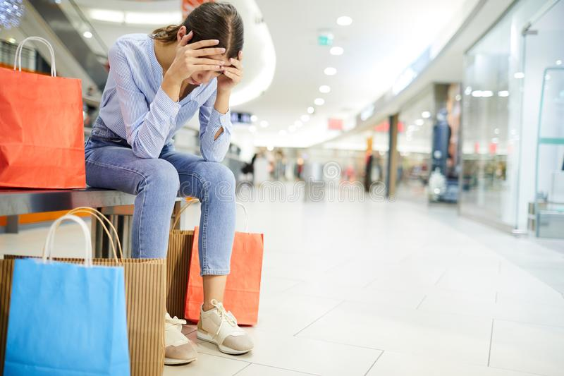 Exhausting shopping. Tired shopper holding by head while sitting on bench among paperbags with purchases in the mall stock photos