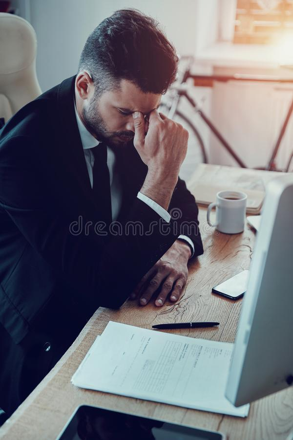 Exhaustion. Tired young man in formalwear massaging nose while sitting in the office royalty free stock photography