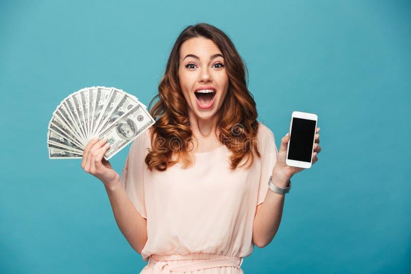 Exhibición emocionada de la demostración de la señora joven del teléfono móvil que sostiene el dinero fotos de archivo libres de regalías