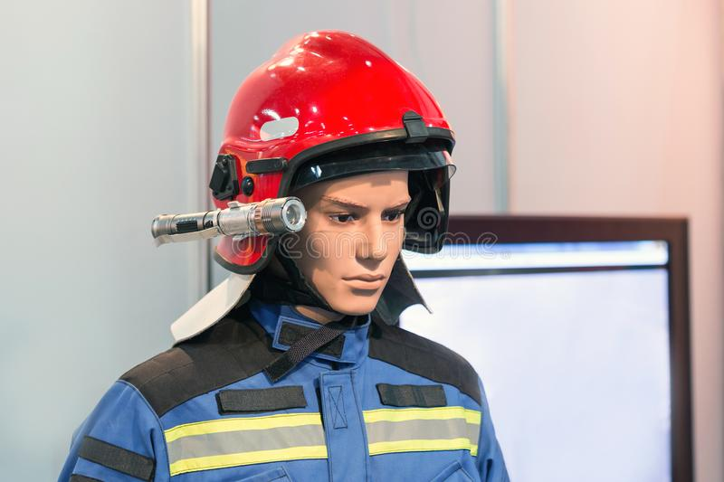 Exhibition firefighter dummy in fire fighter helmet and uniform. Protective rescue wear. Head light torch stock image