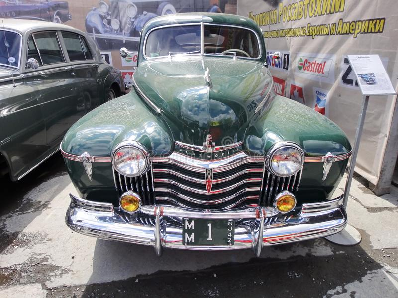 Exhibition of retro cars. Green car `Oldsmobile`, year of manufacture 1941, capacity 115 HP, USA. The oldest American brand stock photography