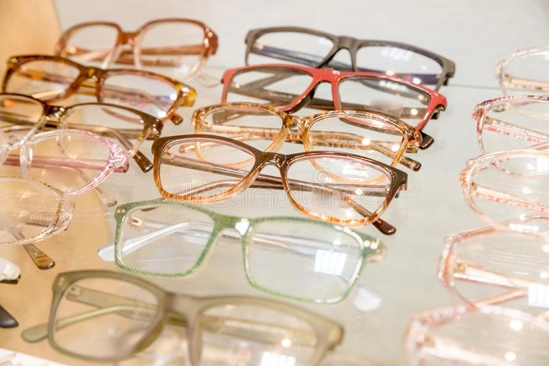 Exhibitor of glasses consisting of shelves of fashionable glasses shown on a wall at the optical shop. optics, health royalty free stock photo