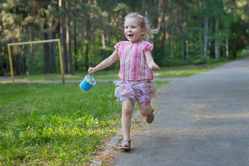 Exhilarated działająca dziewczyna na asfaltu parka footpath mienia pakunku chodniczek pisze kredą zdjęcie royalty free