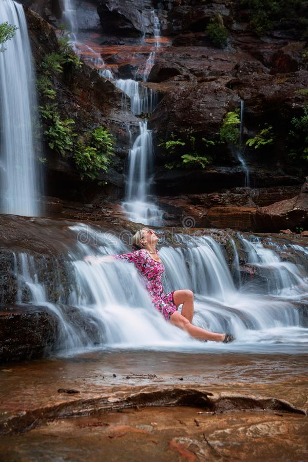 Exhilaration in mountain waterfall, female sitting in flowing ca royalty free stock images