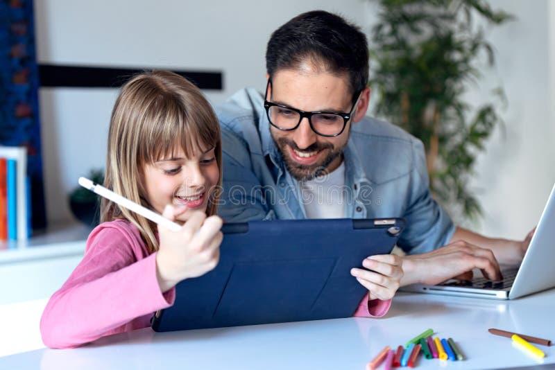 Exibição bonita da menina a seu pai a imagem ela apenas que tira na tabuleta digital em casa imagem de stock