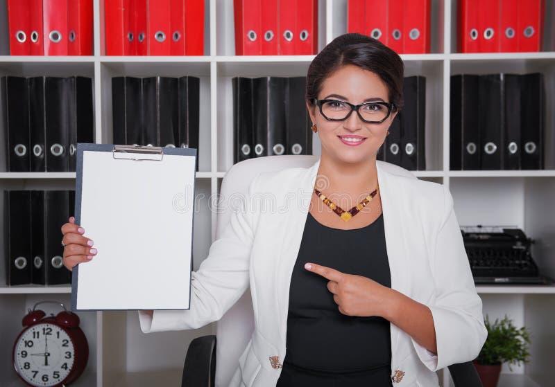 Exibição bonita feliz da mulher de negócio no papel vazio no escritório imagens de stock