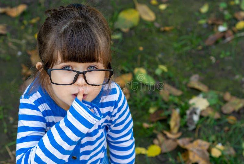 A exibição carismática da criança cala o gesto que esconde a surpresa de preparação secreta que está amigável e entusiástica, foto de stock