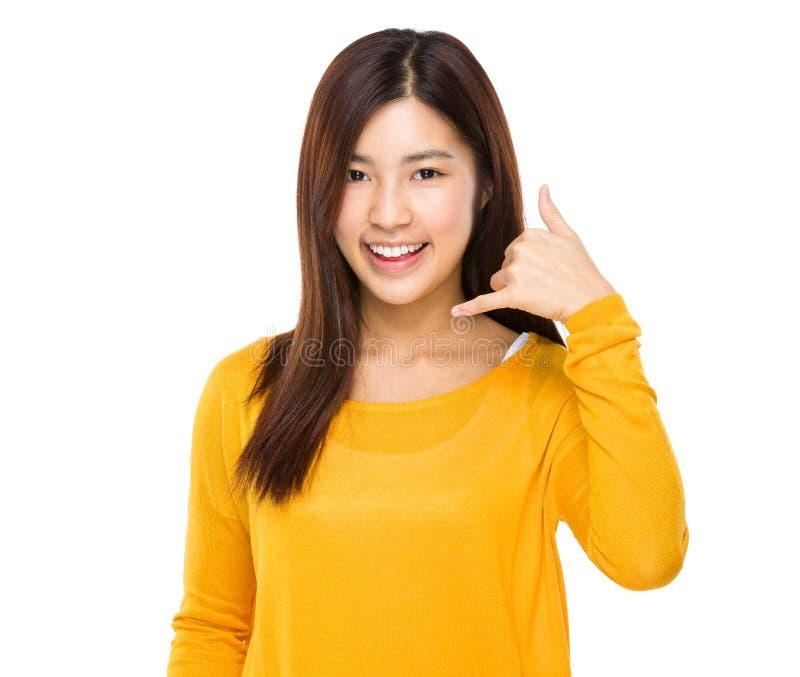 A exibição da mulher chama-me sorriso do sinal da mão do telefone feliz imagem de stock royalty free