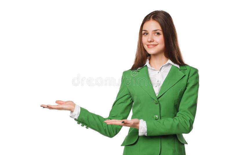 A exibição de sorriso da mulher abre a palma da mão com espaço da cópia para o produto ou o texto Mulher de negócio no terno verd imagens de stock royalty free