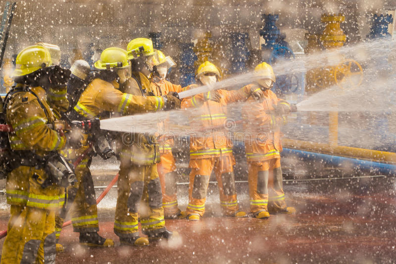 Exibição do bombeiro como usar sistemas de extinção de incêndios de um fogo em um fogo do treinamento foto de stock royalty free