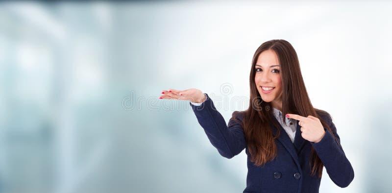 Exibição e apontar de sorriso da mulher fotografia de stock royalty free
