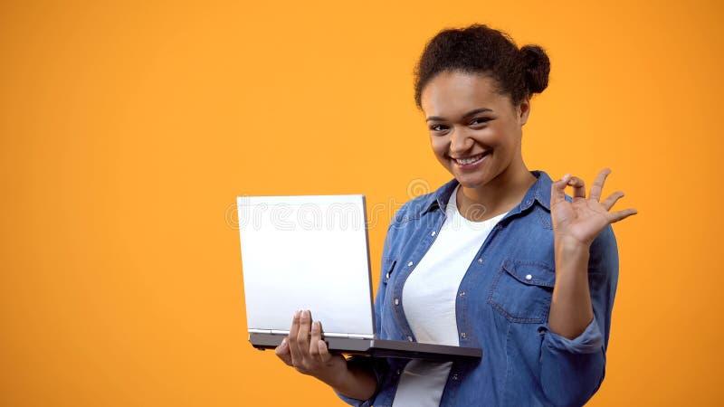 A exibição fêmea nova atrativa da mão do portátil aprova o sinal, satisfeito com a conexão fotos de stock