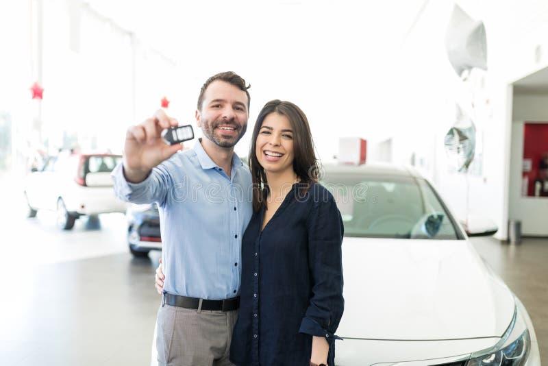 Exibição latino-americano dos pares fora das chaves novas do carro com orgulho imagens de stock royalty free