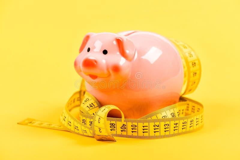 exigency paga baja Dinero del ahorro dep?sito dieta del dinero Finanzas y comercio hucha con la cinta de la medida moneybox imagen de archivo