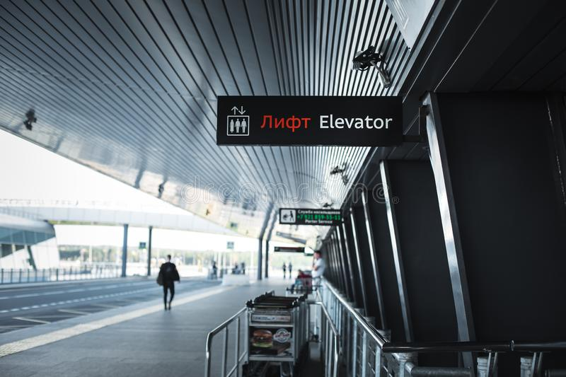 The exit of the airport Pulkovo in Saint-Petersburg-the building of the airport with a signage and Luggage trolleys and the road royalty free stock photo