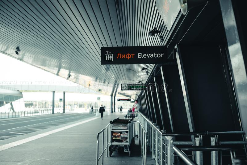 The exit of the airport Pulkovo in Saint-Petersburg-the building of the airport with a signage and Luggage trolleys and the road stock images