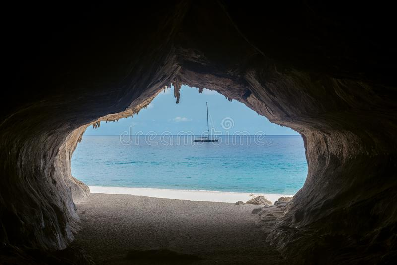 Exit from the cave overlooking beautiful sea and boat at Cala Luna beach royalty free stock photo