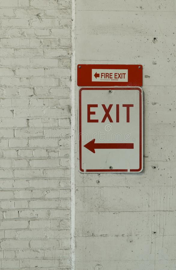 An Exit and Fire Exit sign in a parking garage stock image