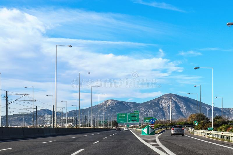 Exit on highway in Greece leaving Athens toward the Peloponnese Peninsula with mountains in the background and signs in Greek and stock image