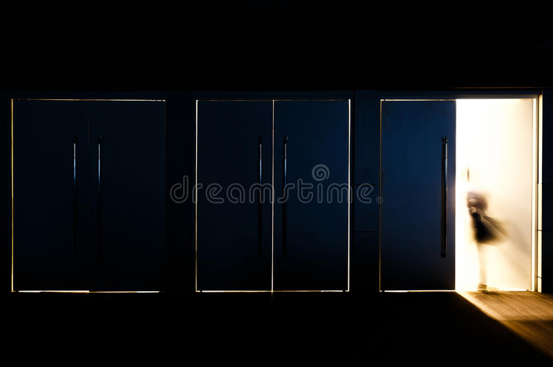 Exit of life. Door opened with motion blur of a man and light coming through the space royalty free stock photo