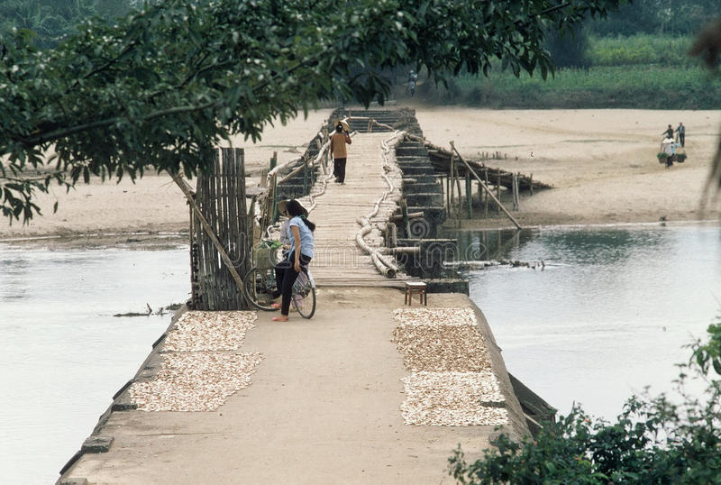 Exit ramp on a bridge to nowhere. A woman dries her haul of tapioca, as a woman crosses a long ago bombed out bridge in northern Vietnam, reinforced and made royalty free stock photography