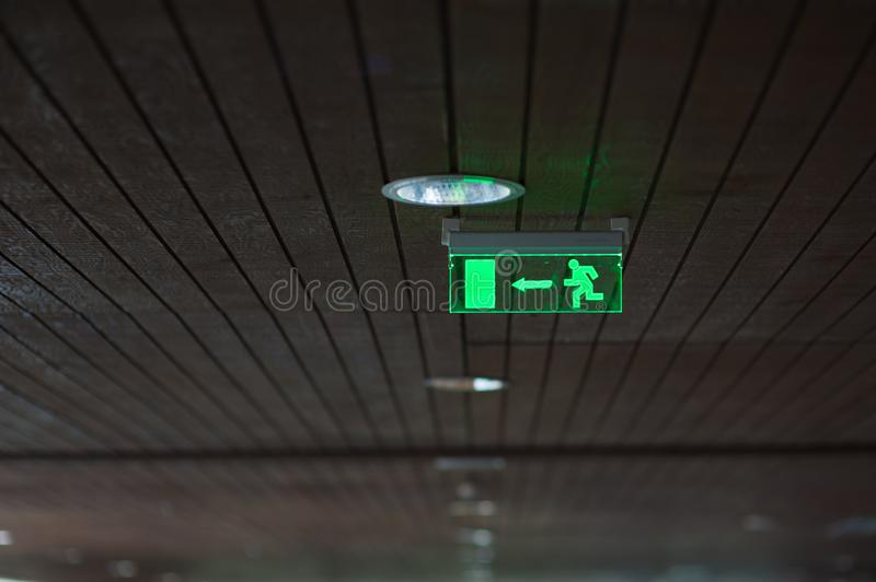 The exit sign of the building glows green.  stock image