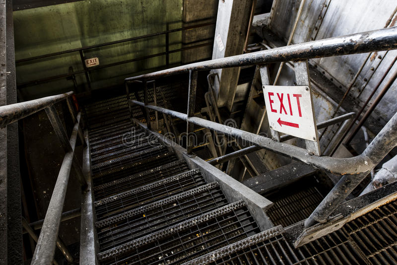 Exit Sign on Staircase in Abandoned Power Plant - New York. An exit sign on a steel staircase in an abandoned power plant in New York stock photography