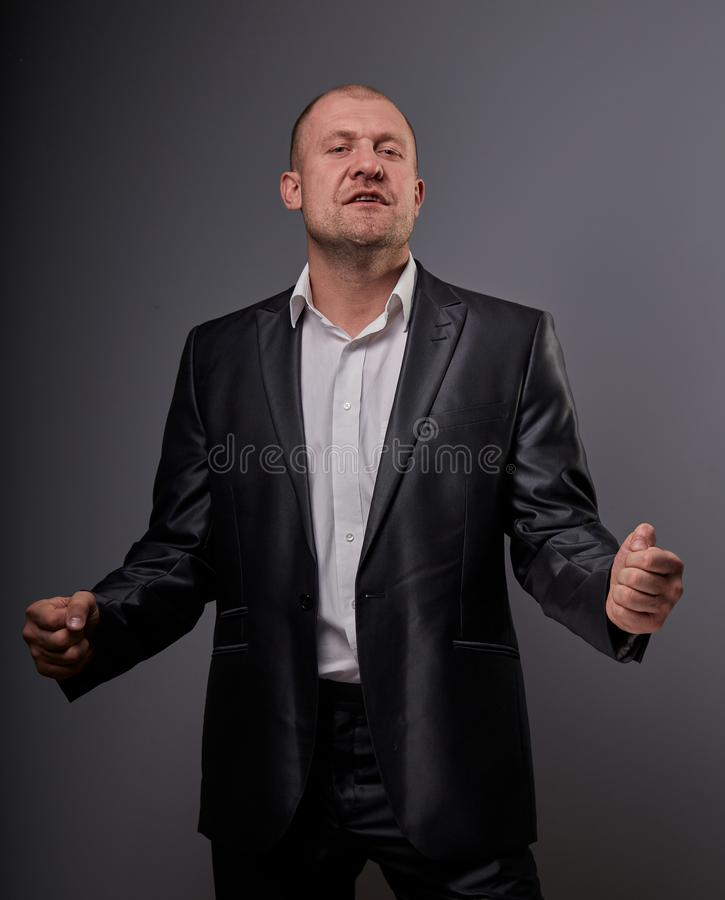 Exited comic bald business man in black suit showing the hands success sign on grey background. Closeup stock photo