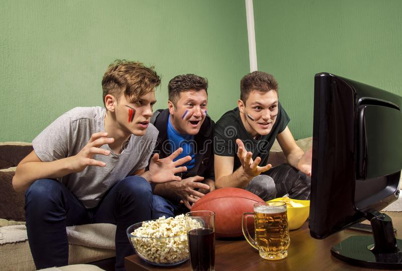Exited family , father and sons watching football royalty free stock image