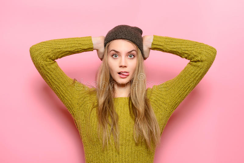 Exited Hipster girl having fun showing tongue wearing casual outfit posing near pink wall stock photos