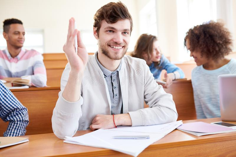 Exited student having question. Cheerful excited handsome bearded student boy sitting at wooden desk with open workbook and raising hand while having question to stock photo