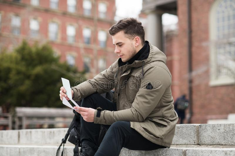 Exited student man reads approval letter after college exams or job offer sitting in campus. Exited student man reads approval letter after college exams or job stock images
